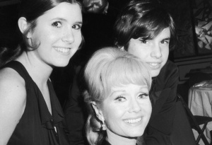 13th March 1973:  American actor Debbie Reynolds sits and smiles with her children, actor Carrie Fisher and Todd Fisher, as they attend the opening night party for the Broadway musical revival 'Irene,' in which Reynolds starred, New York City. The music was composed by Hal Tierney, with lyrics by Joseph McCarthy.  (Photo by Tim Boxer/Hulton Archive/Getty Images)