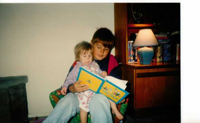 Eldest Son reading to Aspie D - Another favourite, Curious George.  Extra lighting needed! 1993. (c) Sherri Matthews 2014